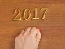 Mão e números 2017 na porta - fundo do ano novo Fotografia de Stock Royalty Free