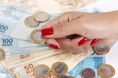 A mão e o dinheiro brasileiro da mulher Imagens de Stock Royalty Free