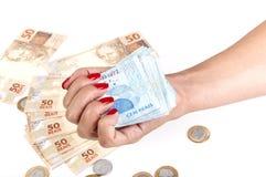 A mão e o dinheiro brasileiro da mulher Fotografia de Stock