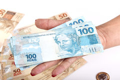 A mão e o dinheiro brasileiro da mulher Imagem de Stock Royalty Free