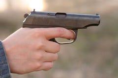 A mão e uma arma do homem imagens de stock