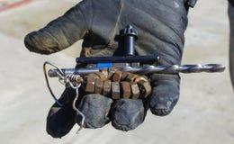 A mão em luvas da construção guarda o equipamento Fotos de Stock