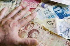 Mão em notas de banco israelitas velhas Imagens de Stock