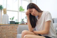 Mão em templos da menina asiática da tristeza infeliz nova que senta-se no sofá Está sentindo não muito bom devido a sua doença e imagens de stock