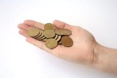 Mão em um fundo branco que guarda um punhado das moedas um hryvni Foto de Stock