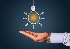 Mão em um fundo do azul do conceito das ilustrações do bulbo da ideia Foto de Stock