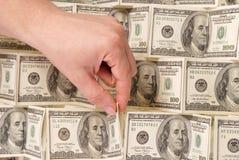 Mão em um fundo do dinheiro Imagens de Stock Royalty Free