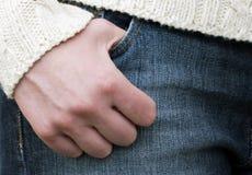 Mão em um par de calças de brim Imagens de Stock