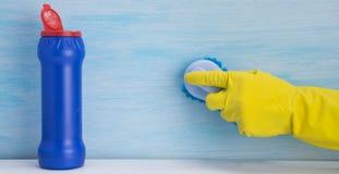 Mão em uma luva amarela que escova a superfície, estando ao lado de um frasco azul com agente de limpeza, em um fundo claro fotos de stock royalty free