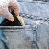 A mão em uma luva branca retira uma carteira com dinheiro, de que cola foto de stock