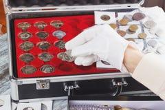 Mão em uma luva com uma moeda de prata imagem de stock