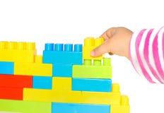 A mão empilha acima o lego ajustado como uma parede no branco imagem de stock