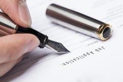a mão enche acima o formulário de candidatura a cargo Imagem de Stock Royalty Free