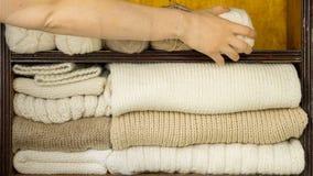 A mão enche prateleiras por bolas das lãs, agulhas de confecção de malhas, telas de lã terminadas video estoque