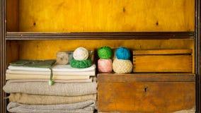A mão enche prateleiras por materiais e por ferramentas para feito a mão, o bordado e a confecção de malhas filme