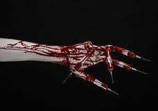 Mão ensanguentado com a seringa nos dedos, seringas dos dedos do pé, seringas da mão, mão ensanguentado horrívea, tema do Dia das Foto de Stock
