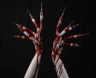 Mão ensanguentado com a seringa nos dedos, seringas dos dedos do pé, seringas da mão, mão ensanguentado horrívea, tema do Dia das Imagens de Stock