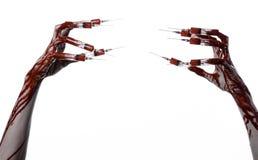 Mão ensanguentado com a seringa nos dedos, seringas dos dedos do pé, seringas da mão, mão ensanguentado horrívea, tema do Dia das Fotografia de Stock