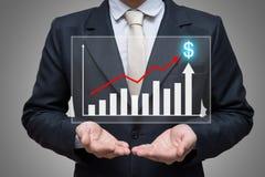 Mão ereta da postura do homem de negócios que guarda a finança do gráfico Fotografia de Stock Royalty Free
