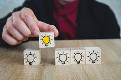 A mão escolheu cubos de madeira com o símbolo amarelo da ampola na tabela de madeira Ideia, conceitos novos da inova??o e da solu fotos de stock