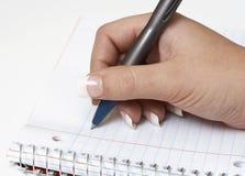A mão escreve imagem de stock