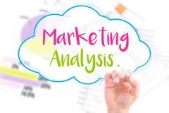 A mão escreve a análise de mercado Foto de Stock