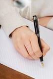 A mão escreve com uma pena em um caderno Imagem de Stock Royalty Free