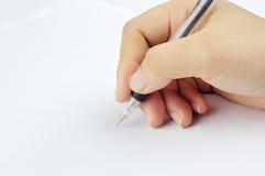 A mão escreve no papel Foto de Stock