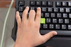 A mão esquerda asiática da criança e usa seu dedo para pressionar no keyboa do jogo Fotos de Stock