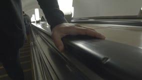 A mão esquerda de homem de jovens que guarda sobre o corrimão da escada rolante no movimento lento do metro video estoque