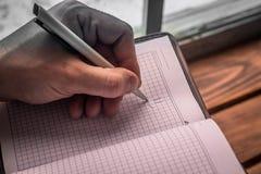 Mão esquerda do ` s dos homens com sorriso do desenho da pena no bloco de notas Imagem de Stock