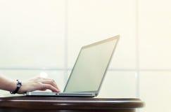 A mão está datilografando no portátil na tabela de madeira na soleira branca fotografia de stock