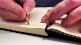 A mão está escrevendo no papel video estoque