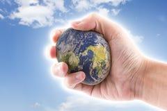 A mão está guardando ao mundo de pedra no céu azul Fotografia de Stock Royalty Free