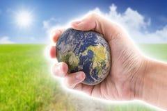 A mão está guardando ao mundo de pedra no céu azul Imagens de Stock Royalty Free