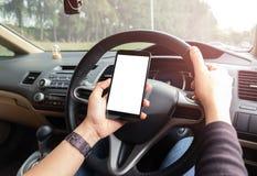 A mão está guardando um telefone do toque com a tela isolada no carro fotografia de stock