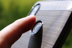 A mão está guardando um telefone preto e o indicador está tocando no varredor da impressão digital para destravar o smartphone imagens de stock