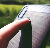 A mão está guardando um telefone preto e o indicador está tocando no varredor da impressão digital para destravar o smartphone imagem de stock