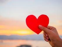 A mão está levantando o coração de papel vermelho com luz solar do borrão durante o por do sol, Fotografia de Stock