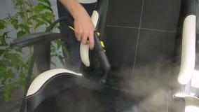 A mão está limpando a cadeira do escritório com um líquido de limpeza do vapor Conceito home da limpeza vídeos de arquivo