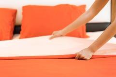 A mão estabelece a folha de cama branca no hotel da sala fotos de stock royalty free