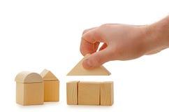 A mão estabelece um telhado do brinquedo em cubos de madeira Imagem de Stock Royalty Free
