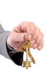 Mão executiva masculina dos bens imobiliários que prende duas chaves. Fotografia de Stock