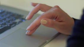A mão fêmea à moda com laca amarela em pregos toca no painel de toque video estoque