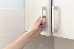 A mão fêmea abre as portas do armário, fim acima Imagens de Stock
