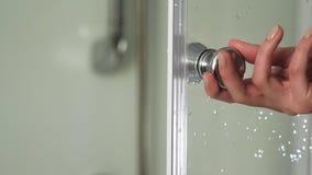 A mão fêmea abre a porta na cabine do chuveiro Cabine do banheiro do punho da posse da mulher com assistente Detalhe de um modern vídeos de arquivo