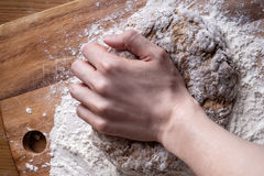 A mão fêmea amassa a massa para o pão Fotos de Stock
