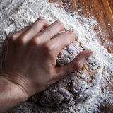 A mão fêmea amassa a massa para o pão Fotos de Stock Royalty Free