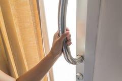 Mão fêmea asiática que guarda o suporte de aço inoxidável da porta imagem de stock royalty free