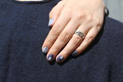 Mão fêmea bonita com tratamento de mãos extraordinário Projeto criativo do prego no azul Cores ultra à moda do verniz para as unh Imagens de Stock
